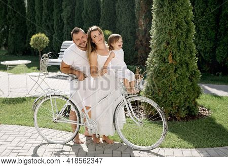 Mom And Dad Ride Their Daughter In A Basket On A Bicycle. Family Vacation. The Child Is Happy And La