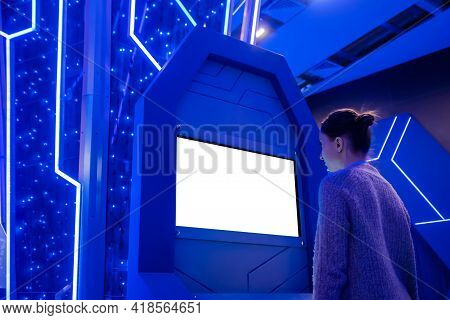 Woman Looking At Blank Digital Interactive White Display Kiosk At Exhibition Or Museum With Futurist