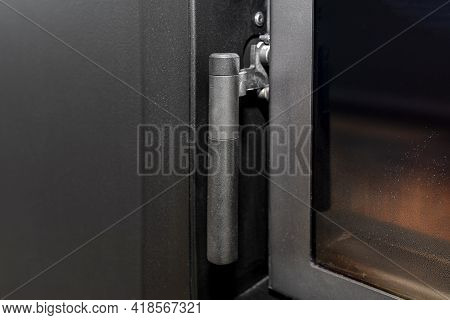 A Handle And A Closure In One In A Modern Fireplace With A Closed Combustion Chamber Standing In The