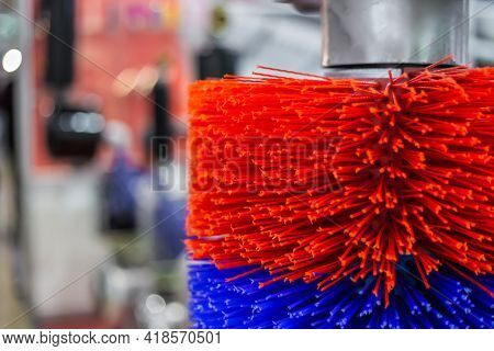 Close Up: Automatic Red And Blue Swinging Brush For Cleaning Cows At Agricultural Exhibition. Farmin