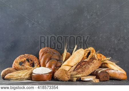 Assortment Of Various Delicious Freshly Baked Bread, On Black Concrete Background Top View Copy Spac