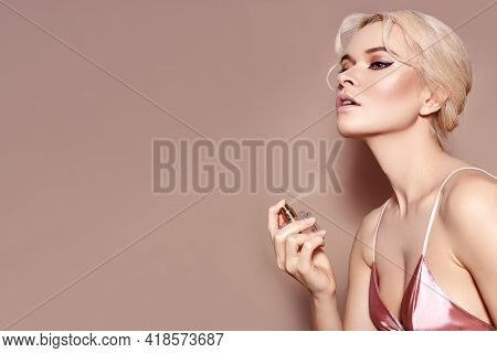 Beautiful Woman Applying Perfume Spray On Neck. Blond Model With Sexy Retro Make-up In Pink Lingerie