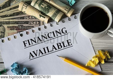 Financing Available - Words On A White Sheet Against A Background Of Banknotes, Cups Of Coffee And P