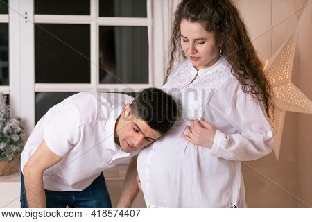 Smiling Man Listening To The Belly Of Pregnant Woman. Happy Family In Expectation, Waiting The Baby.