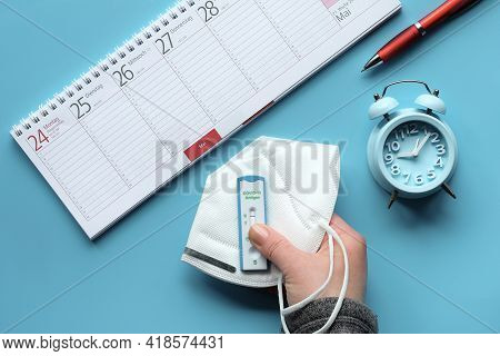 Week Planner, Schnelltest, Rapid Corona Test In German Language. Flat Lay With Hand Holding Express
