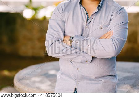 Man In A Blue Shirt With His Arms Crossed On His Chest Leans On A Stone Table