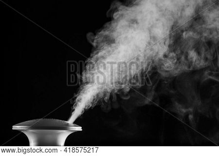 Steam-generator Sprays White Cloud Of Steam Isolated On Black Background