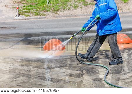 A Janitor In A Blue Jacket Pours Water From A Spray Bottle On The Sidewalk And Flushes The Dirt Onto