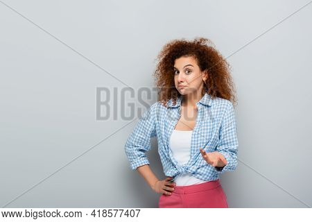 Discouraged Woman Pointing With Hand While Looking At Camera On Grey Background.