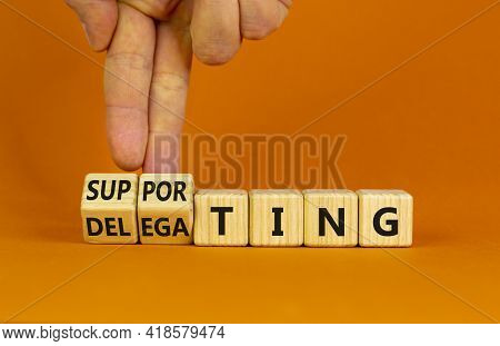 Delegating Or Supporting Leadership Style Symbol. Businessman Turns Cubes, Changes Words Supporting