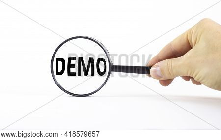 Demo Symbol. Magnifying Glass With Word Demo On A Beautiful White Background. Businessman Hand. Busi