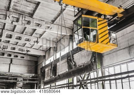 Overhead Crane Hoist Equipment In An Industrial Plant Transports An Iron Rail On Lifting Chain.