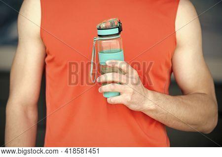 Hand Holds Sportive Bottle Of Water Or Sport Drink, Male Body Background. Bottle Of Water In Muscula