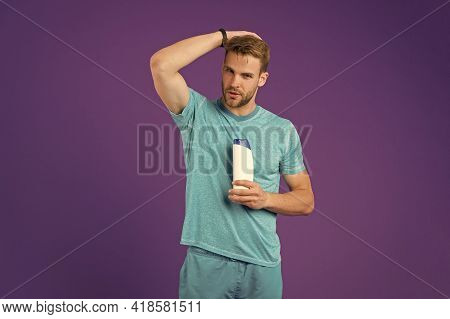Man On Confident Face Touching His Hair, Violet Background. Guy With Bristle Holds Bottle With Shamp