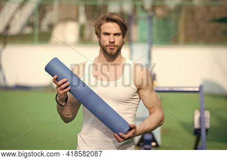 Practicing Yoga. Sportsman Carries Yoga Mat For Outdoor Practicing. Outdoor Yoga Concept. Man Athlet