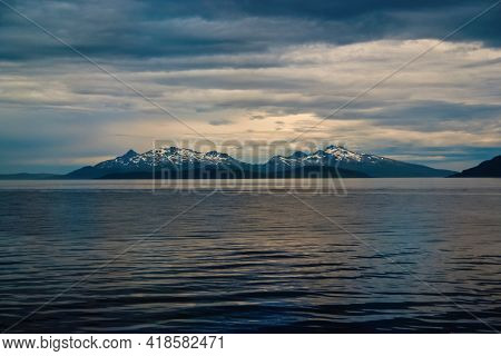 Sea In Hammerfest, Norway. Evening Seascape With Mountain Coast Under Cloudy Sky. Sea Travelling. Ad