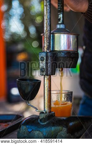 Close-up Of A Man Crushes Juice From A Fresh Bright Orange. Cooking Freshly Squeezed Orange Juice Wi