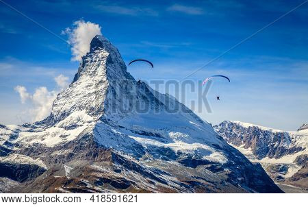 Two paragliders over Swiss Alps with Matterhorn in the background