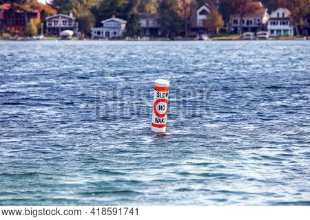 No wake zone buoy float on a lake with cottages in the background