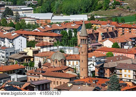 View from above of houses with red roofs and belfry of Madonna della Moretta church in town of Alba, Piedmont, Northern Italy.