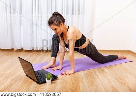 Fit Woman Doing Yoga And Watching Online Tutorials On Laptop. Attractive Young Woman Doing Yoga And