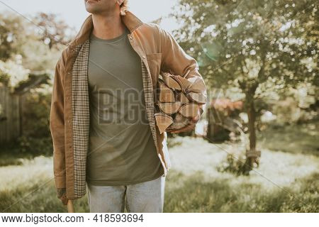 Man standing with axe and chopped lumber and stump on a farm