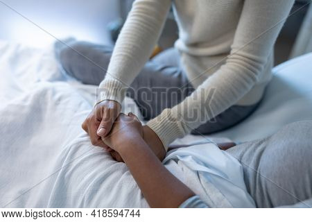 Midsection of mixed race mother comforting sick daughter, sitting on hospital bed holding her hands. medicine, health and healthcare services.