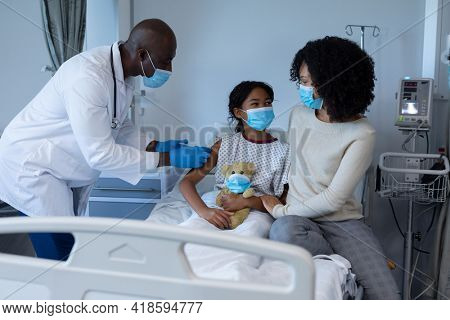 Male doctor giving covid vaccination to sick girl in hospital bed with mother, all in face masks. medicine, health and healthcare services during coronavirus covid 19 pandemic.