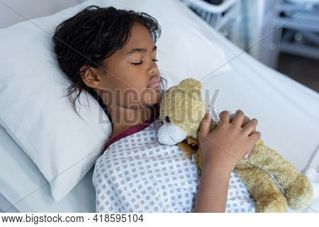 Mixed race sick girl holding teddy bear lying asleep in bed in a hospital ward. medicine, health and healthcare services.