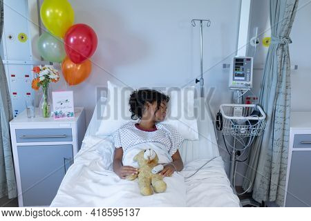 Sick mixed race girl asleep in hospital bed wearing fingertip pulse oximeter and holding teddy bear. medicine, health and healthcare services.