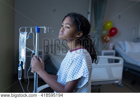 Bored sick mixed race girl standing in hospital ward with iv drip bag on stand looking out of window. medicine, health and healthcare services.