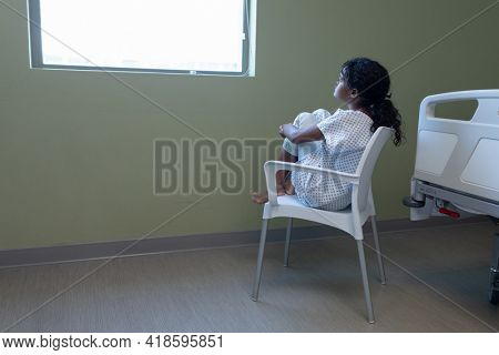 Bored sick mixed race girl sitting on chair in hospital ward looking out of window. medicine, health and healthcare services.