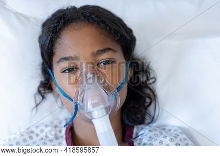 Portrait of sick mixed race girl lying in hospital bed wearing oxygen mask ventilator. medicine, health and healthcare services during coronavirus covid 19 pandemic.