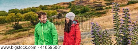New Zealand travel - couple tourists hiking at nature view of Lake Pukaki near Aoraki aka Mount Cook, a famous travel road trip tourist destination. Panoramic banner of young couple hiking in nature.