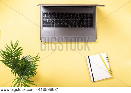 Notebook And Notebook With Pencil. Computer And Notebook. A Flowerpot Near The Computer.