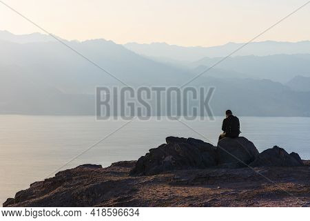 A Man Sits On A High Mountain Cliff And Overlooks The Horizon. A Concept For Hope, Peace, Power, Sou