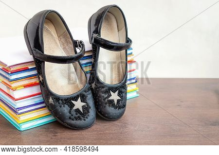 Close-up And Selective Focus Of Black Old Worn Children's Shoes On Stack Of Books Lying On Wooden Ta