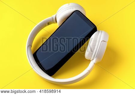 Close-up And Selective Focus Of The Phone And White Wireless Headphones On A Bright Yellow Backgroun