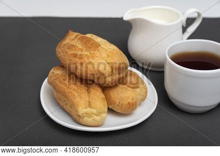 Eclairs And Tea With Milk. Traditional French Eclairs. Profiteroles On White Saucer