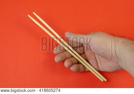 A Man's Hand Holds Wooden Chopsticks Against A Red Background. Culture And Cuisine Of The World Conc