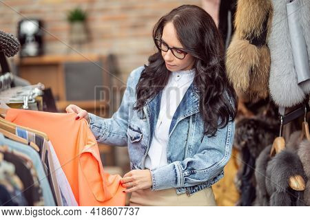 Brunette Wearing Glasses Looks At Clothes On The Rack In The Fashion Store.