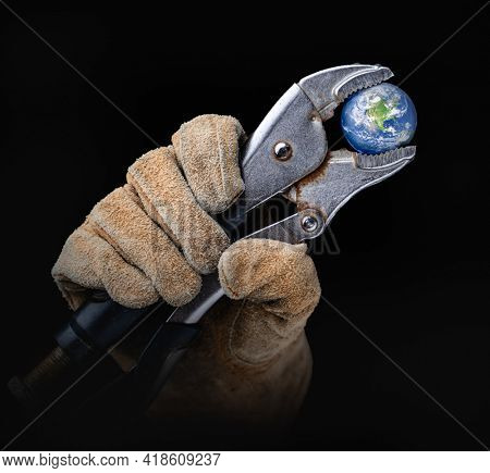 Worker In Construction Gloves Holding  Planet Earth with  Vise-grip Wrench.