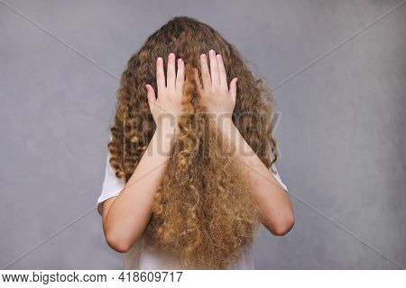 A Girl Covering Her Face With Her Hands And Hair. The Figure Of A Girl Without A Face, Her Face Hidd