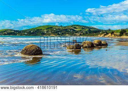 Blue sky reflected in the wet sand. Moeraki's huge round boulders on a sandy beach. The Pacific ocean tide begins. New Zealand. The concept of ecological, exotic and phototourism