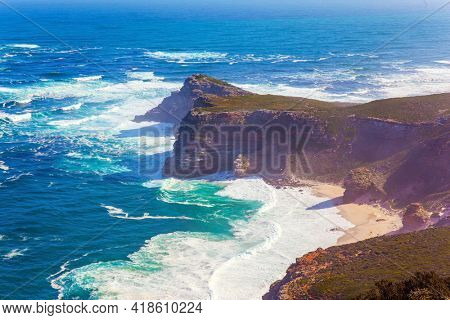 Bird's-eye view. South Africa. Cape of Good Hope at the southern tip of the Cape Peninsula. Powerful ocean surf. White foam of the ocean surf. Bright sunny summer february day