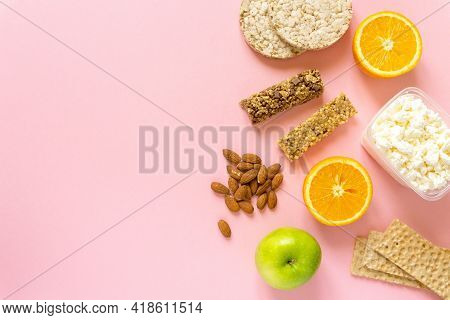 Flat Lay Of Healthy Snacks. Fruits, Muesli Bars, Crispbreads, Cottage Cheese And Nuts On Pink Backgr