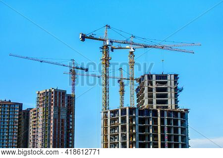 Four Tower Cranes Are Working Near Complex Of New High-rise Buildings Under Construction. Clear Blue