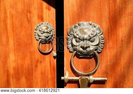 Chinese Lion Head Knocker On Wooden Door