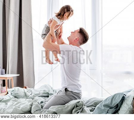 Young father sitting in the bed and spending morning with his little daughter holding her in his hands against the window. Smiling child with her parent in sunny room with stylish interior