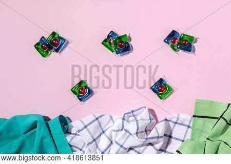 Laundry Capsules And Towels On Light Pink Background, Flat Lay. Concept Of Maintaining Cleanliness A